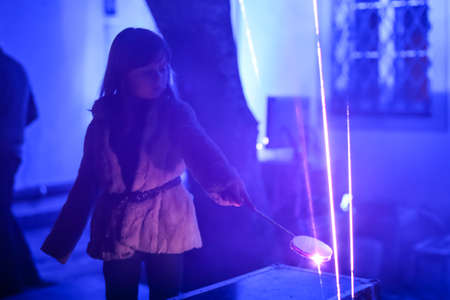 Zagreb, Croatia - 19 March, 2017 : Festival of lights in Zagreb, Croatia. A young girl plays by interrupting laser beams in Zagreb, Croatia. 報道画像