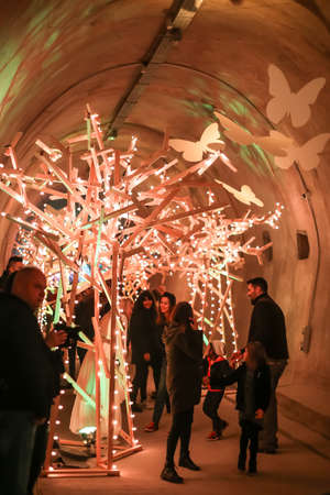 Zagreb, Croatia - 19 March, 2017 : Festival of lights in Zagreb, Croatia. People walking through a lighted tunnel Gric with lighted colorful wood shaped sculpture in the center of Zagreb. 報道画像