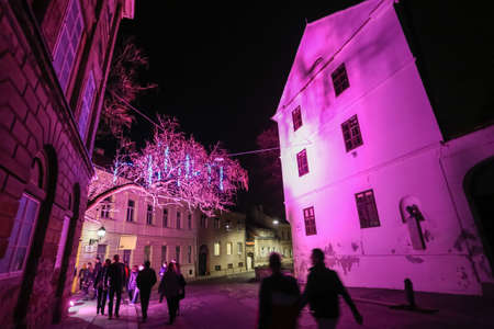 Zagreb, Croatia - 24 March, 2019 : People walking by illuminated building in the upper town during Festival of lights in Zagreb, Croatia.