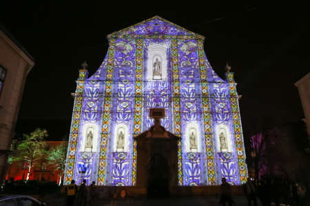 Zagreb, Croatia - 24 March, 2019 : Festival of lights in Zagreb, Croatia. People walking next to illuminated with a drawing church of St. Catherine in the upper town.