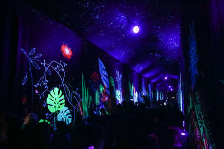 Zagreb,Croatia - 24 March, 2019 : People walking through the illuminated tunnel with ultraviolet light that illuminates the drawings on the canvas along the tunnel during Festival of lights in Zagreb.