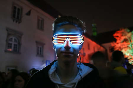 Zagreb, Croatia - 24 March, 2019 : A man with lighted glasses during Festival of lights in upper town in Zagreb, Croatia.