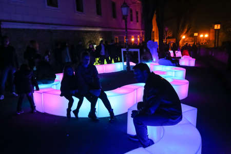 Zagreb, Croatia - 24 March, 2019 : People sitting on a light installation on the Strossmayer Promenade during Festival of lights in Zagreb.