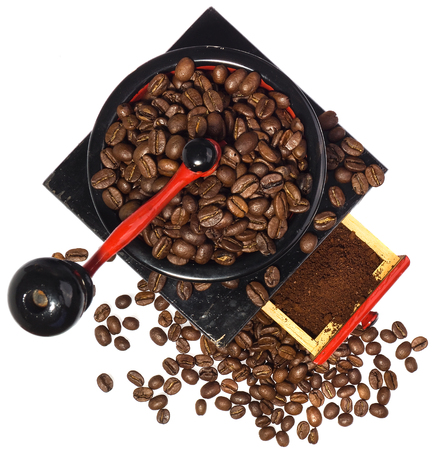 Old coffee grinder during the grinding coffee, top view, white background, coffee beans has spilled Stock Photo