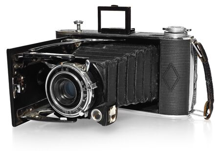 obscura: Old, antique, black, pocket camera. The camera open, ready to take pictures. Visible opening mechanism, lens and adjustable, black leather strap. View at an angle from the side with reflection on white background. Camera model Agfa Billy Record