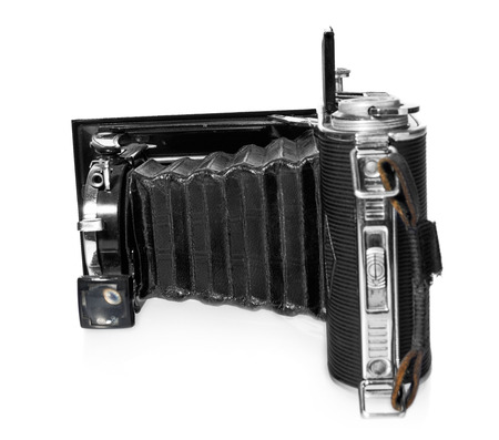 obscura: Old, antique, black, pocket camera. The camera open, side view of the lens and the internal mechanism on a white background with reflection. It has a black leather handle. Camera model Agfa Billy Record. Stock Photo