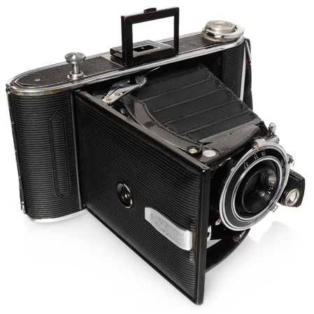 slight: Old, antique, black, pocket camera. The camera open, ready to take pictures. View at an angle from above with a slight reflection on a white background. Camera model Agfa Billy Record.