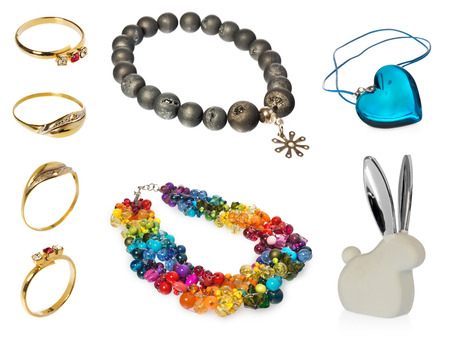 small articles: composition of jewelry - Blue crystal heart pendant - Bunny ears with silver - Necklace with olive beads - necklace with colored crystals and beads - Gold rings engraved, diamonds and ruby ??Objects on white background with light shadow and reflection.