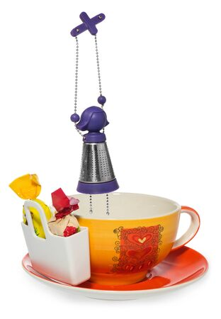 Empty coffee, tea cup with purple silver infuser in the shape of a girl on a chain and storage on candy with two sweets . Cup and saucer decorated with hearts in color yellow, orange, red. Container for sweetmeats  in white. Candy in yellow, cream, red. D Stock Photo