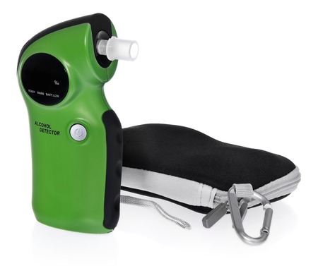 Alcohol detector with case. The device in the color green, black, packaging gray, black. The composition on a white background with slight shadow.