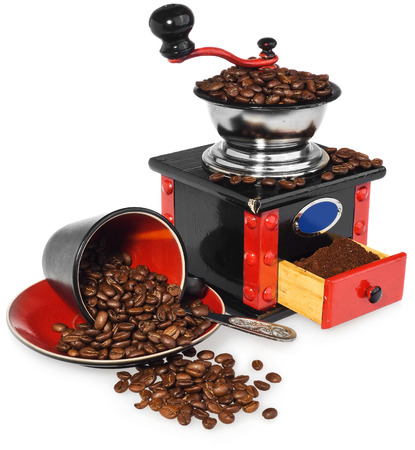 Old antique wooden coffee grinder. Coffee mill hand-painted in black, red and blue. Next to the mill black and red cup, silver spoon and spilled coffee beans. The whole composition, isolated on white background with light shadow and reflection. Stock Photo