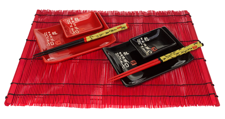Red and black set of dishes for sushi on the red wooden mat. Sushi set consists of plates, saucers, bowls and chopsticks. Tableware on a white background.