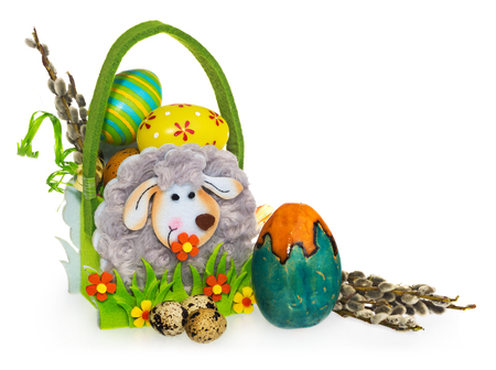 slight: Basket with easter eggs and catkins. Easter basket made of felt, decorated with lamb, with flowers. Eggs in many designs, patterns and colors. Composition on a white background with a slight shadow.