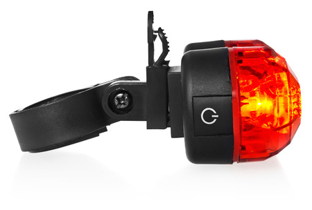 Illuminated rear bike lamp. Lighting in red color. Bicycle mounting black plastic. Equipment on a white background with a slight reflection. Stock fotó