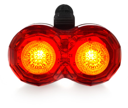 Illuminated rear bike lamp. Lighting in red color. Bicycle mounting black plastic. Equipment on a white background with a slight reflection. Stock Photo