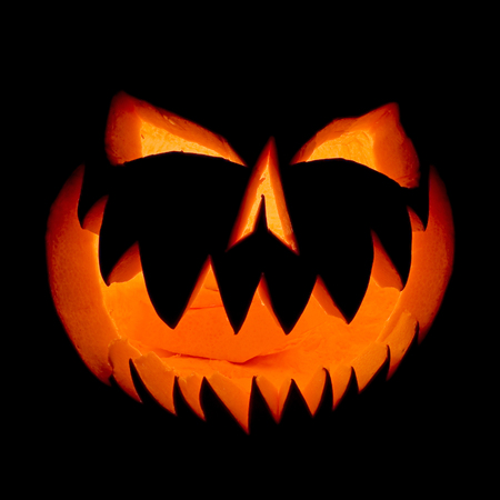 Halloween pumpkin face ghost glowing in the dark. Decoration illuminates and emerges from the darkness. Stock Photo
