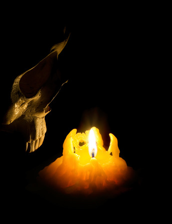 Halloween ghost human skull comes out of darkness. Skeleton head lit with candle. Party decoration  illuminates on a black background. Stock Photo