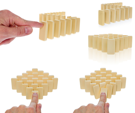 the collapsing: Domino in a creamy color arranged in a row pressed by a finger begins to overturn. The blocks are arranged in front of an empty part. Composition on a white background. Stock Photo