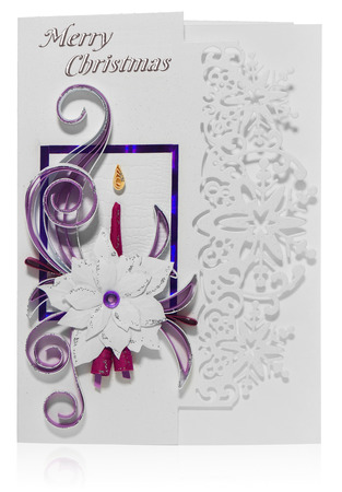 Handmade Christmas card. Postcard with Merry Christmas greetings. Hand decorated card with flower poinsettia, spurge similar, candle and bells. Paper decorations decorated with leaves and folkloric, folk patterns. Card in purple, gold, green, yellow on a white background with a slight reflection.