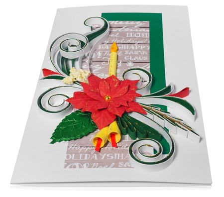 Handmade Christmas card. Postcard with Merry Christmas greetings. Hand decorated card with flower poinsettia, spurge similar, candle and bells. Paper decorations decorated with leaves and folkloric, folk patterns. Card in green, gold, green, yellow on a white background with a slight reflection.