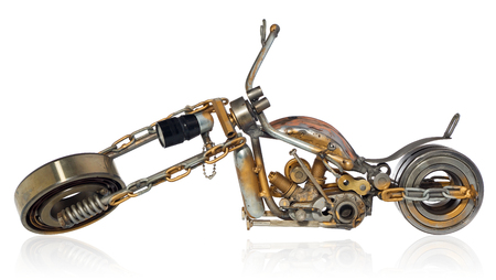 Handmade motorcycle, chopper, cruiser made of metal parts, bearings, screwdrivers, motor candles, wires, chains. A motorbike model isolated on a white background with a slight shadow and reflection. Stock Photo