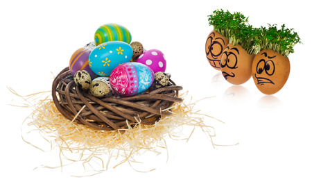 Handpainted Easter eggs in funny scared and surprised cartoonish faces with cress like hair. Handmade eggs look at the outstanding foreign individual egg in the basket. The watercress stylized for the hairstyle of the character.