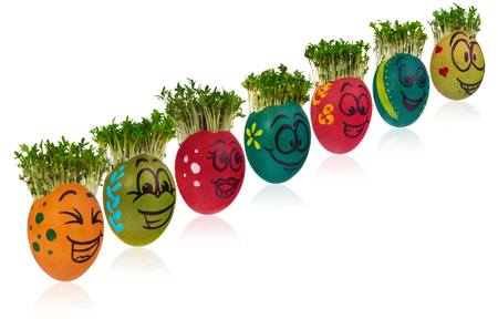 Easter egg painted in a funny smiley girl face and colorful patterns with cress like hair. The watercress stylized for the hairstyle of the character. Egg in red and orange colors on a white background with a slight reflection.