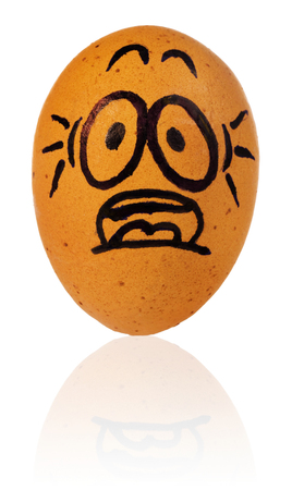 Easter egg, painted in a terrified cartoon funny face of a guy. Decorated scared egg in a natural yellow color. Easter decorations on a white background with a light reflection.