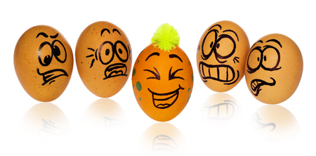 Easter eggs, painted in smiling and terrified cartoon faces. Decorated eggs with funny colorful hairstyles look at one other unique and distinctive Easter egg. Figures on a white background with a light reflection.