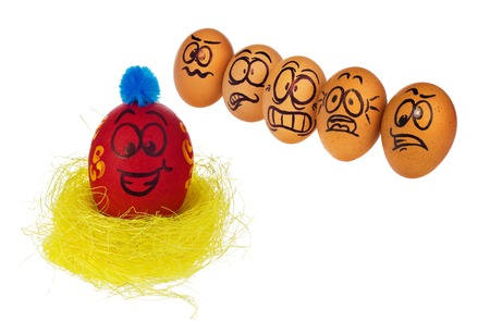 Easter eggs, hand-made painted in various patterns and colors with cartoon faces. Eggs in natural colors look with horror, astonishment and fear at colored smiling face of Easter eggs in a birds nest.