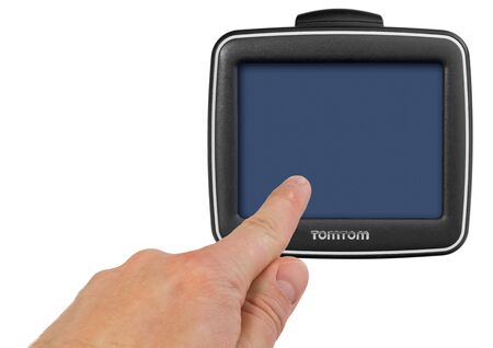TomTom GPS car navigation with handle. The finger indicates the point on the satellite navigation screen. Black electronic map device with blue screen and silver border. Satellite navigation device isolated on white background.