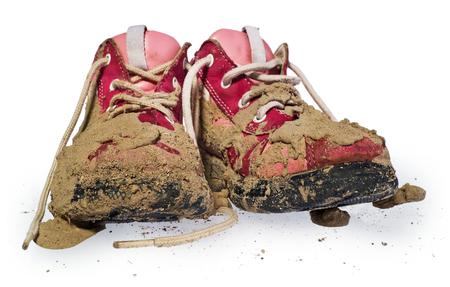 Childrens tiny shoes covered with mud. Dirty leggings for childrens feet in raspberry and white color isolated on a white background.