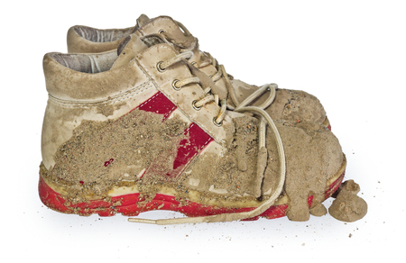 Children's tiny shoes covered with mud. Dirty leggings for children's feet in raspberry and white color isolated on a white background.