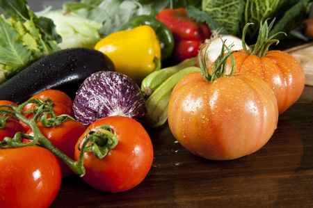 a wooden table spread of fresh vegetables photo