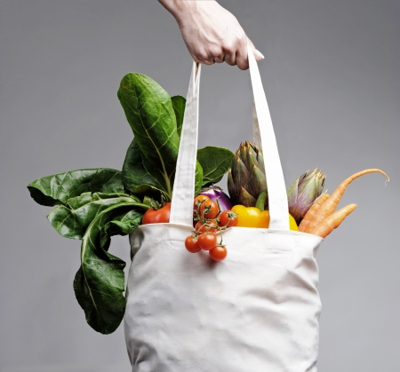 grocery bag: full of vegatables cotton shopping bag carried by a human hand Stock Photo