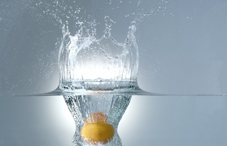 fresh tangerine dropped into water photo