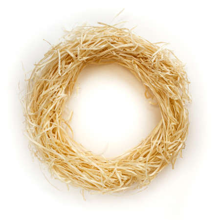 Pile of straw forming a round frame on a white background with a blank space inside. Clean wood shavings coiled in a circle.