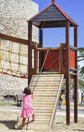 Child girl jungle gym in playground. Outdoor park photo