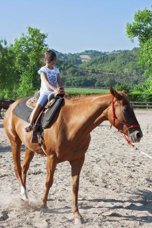 kindergartner: Horse riding - lovely girl is riding a horse Stock Photo