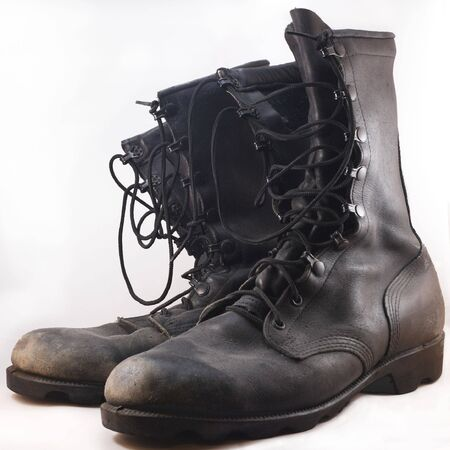 Used black leather combat boots in front of white background photo