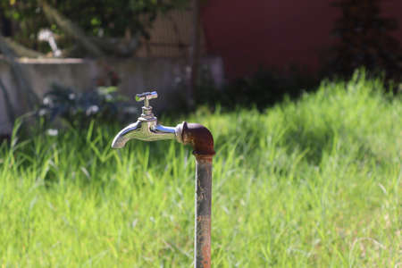 Photo of an outdoor water tap in nature background. Outdoor faucet in the garden. Zdjęcie Seryjne
