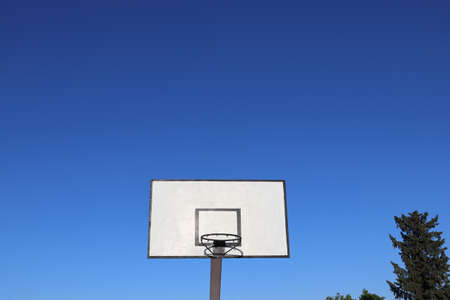 Outdoor basketball hoop with clear blue sky. The concept of outdoor sport equipments in Africa.