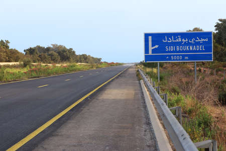 Highway through a town in Morocco on the drive from Tangier to Casablanca. Highway between Kenitra and Rabat. Moroccan road sign.
