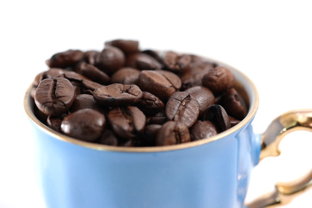 golden bean: A light-blue coffee cup full of coffee beans on white background.