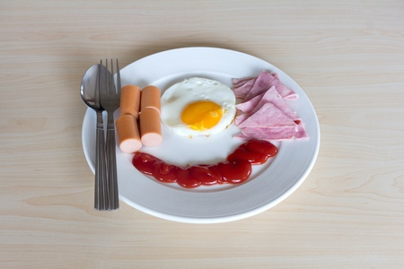 Fried egg hot dog ham and ketchup in plate on woodden table photo