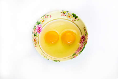 Raw egg in cup isolated on white background photo