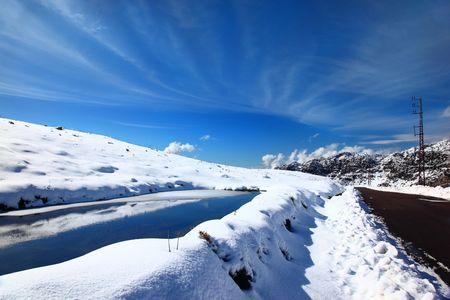 Beautiful winter lake landscape with reflection of blue sky photo