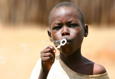 kenya: Portrait of African kid playing a bubbles. Editorial use only