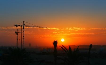 Construction crane over orange sunset sky Stock Photo - 6895388
