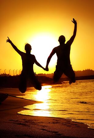 Two happy jumpers on the beach at sunset photo